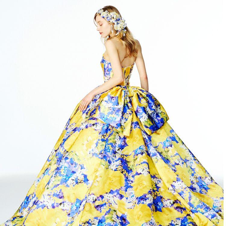 蜷川実花ディレクション「M / mika ninagawa」 7thコレクション   定番となっているグリッター加工のプリンセスドレス。 長いトレーンに大きな後ろリボンが少し甘さをONしたデザインに。 プリントの鮮やかさとグリッターの輝きが合わさった存在感のある1着です。
