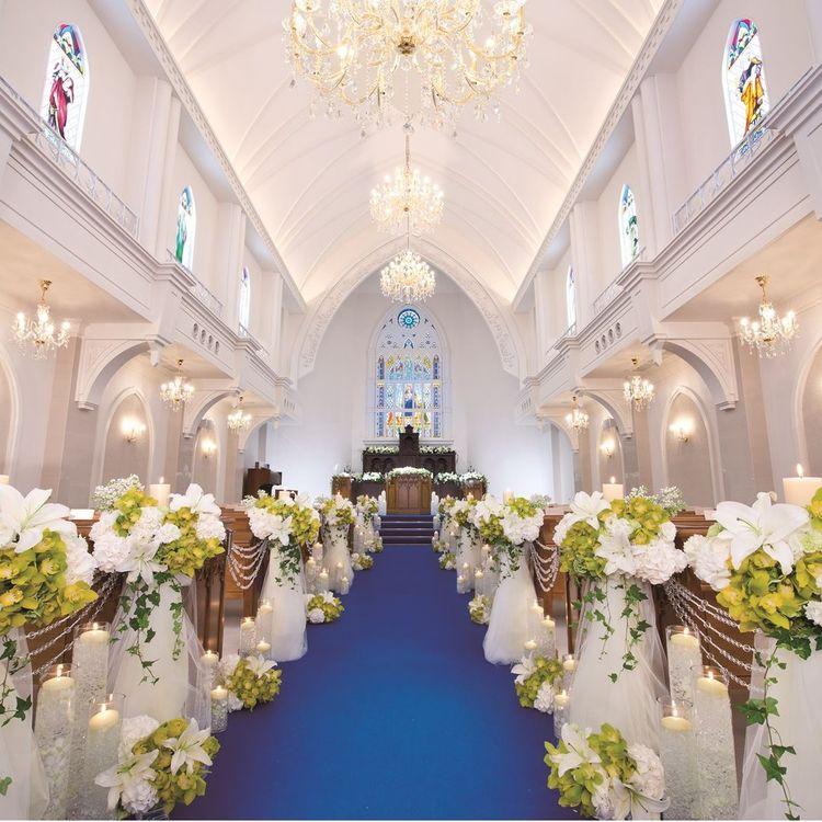 青空のもと、ひときわ目立つ大聖堂。 お母様のベールダウンを終え、チャペルの扉が開くと、目の前にはあたたかい光が差し込むステンドグラスと、真紅のバージンロード。  挙式を終えると、視界いっぱいに広がる青空のもと、ガーデンへとつながる階段でのフラワーシャワーで、おふたりを祝福。  荘厳なチャペルで、結婚式という、おふたりの最高のステージが始まります。