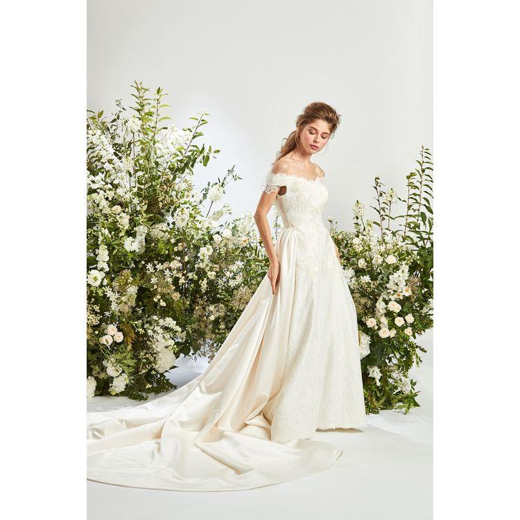 総レースのフショルダードレスにシルクサテンのトレーンが取り付けられたロマンティックでエレガントな1着。シンプルながらにうっとり目を引くドレススタイルです。