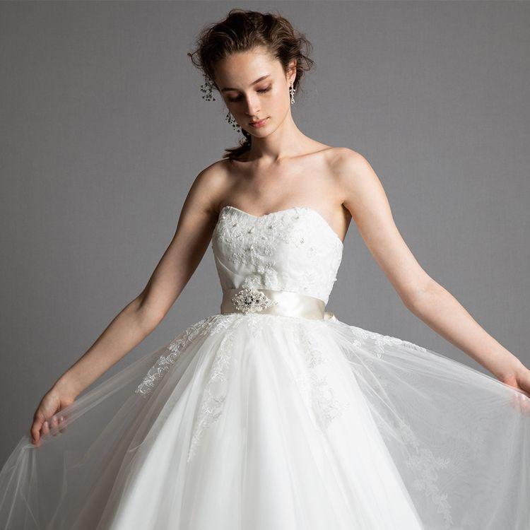 ハートネックラインの胸元と、透明感のあるスカートが素敵な、大人可愛いスタイリッシュなウェディングドレスです。ウェストにはサッシュベルト付けると、引き締め効果抜群で、花嫁のウェストを細くスタイル良く見せてくれます。※サッシュベルト別売   ¥138,000(税抜)
