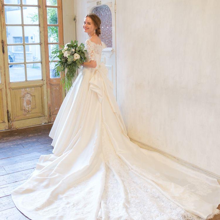 印象的なロングトレーンのウエディングドレスは多くの花嫁が憧れるもの。 袖付きを選べば、クラシカルな美しさを放つバックスタイルに。